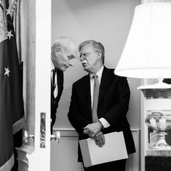 Former White House Chief of Staff John Kelly talks to ex–National Security Adviser John Bolton in a doorway of the White House. President Donald Trump is seen speaking off to the side.